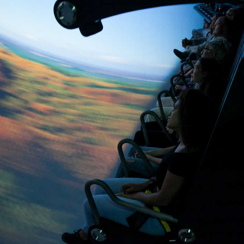 People in the THIS IS HOLLAND attractions with a video view of a Dutch forest in the background.