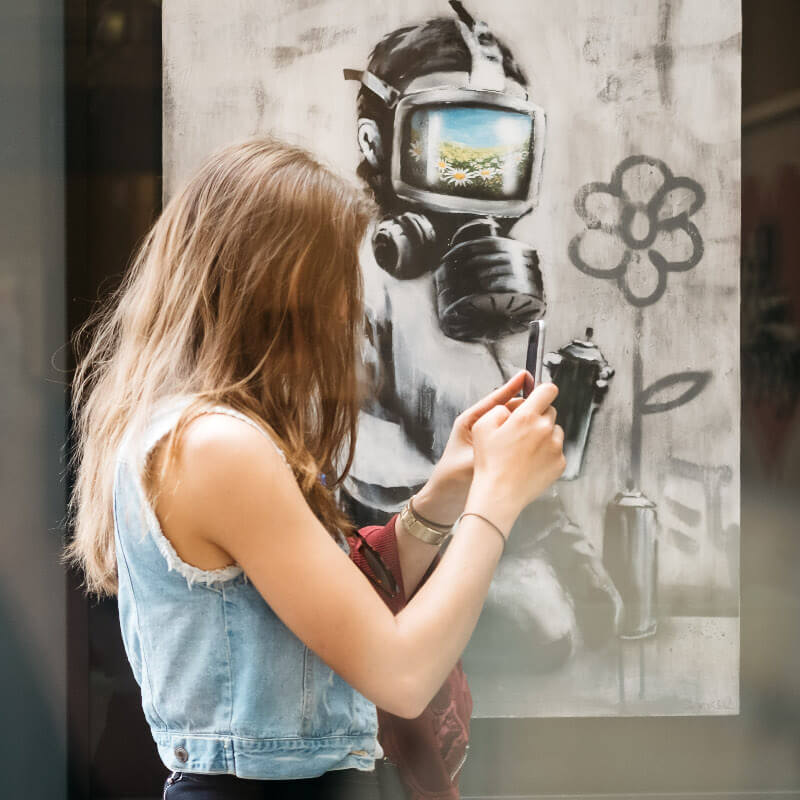A woman taking a picture with her phone while standing in front of a painting of a man with a gas mask at the Moco Museum.