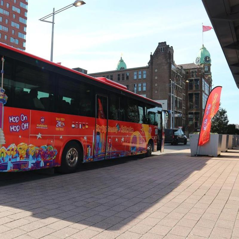 The City Sightseeing Rotterdam bus standing still near a pavement in Rotterdam.