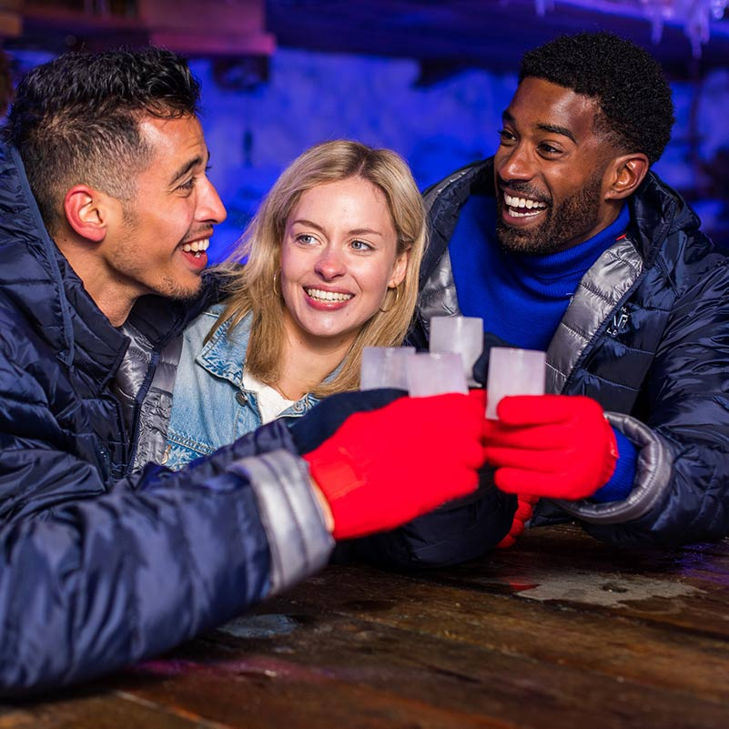 Three people toasting with shot glasses made from ice in the Amsterdam Icebar.