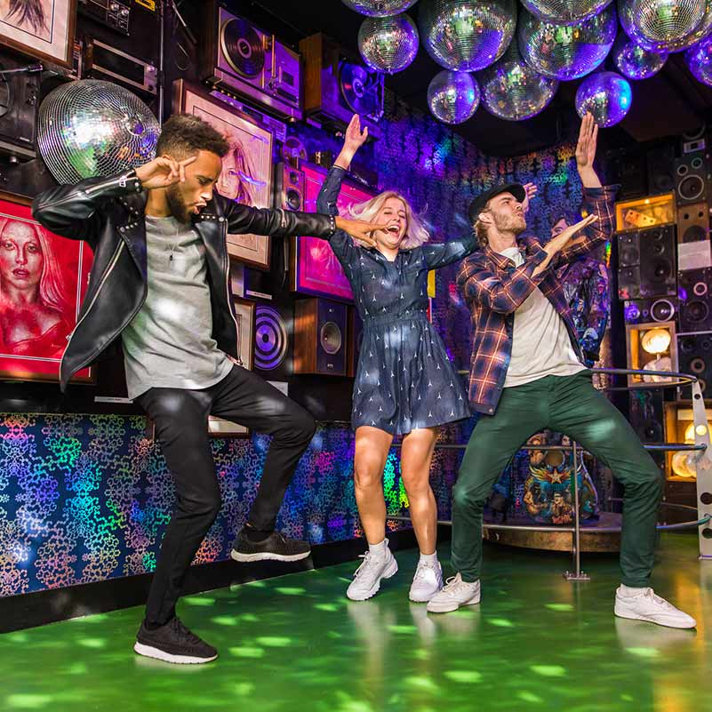 Three people dancing in a disco themed room in Ripley's Believe it or Not Amsterdam.