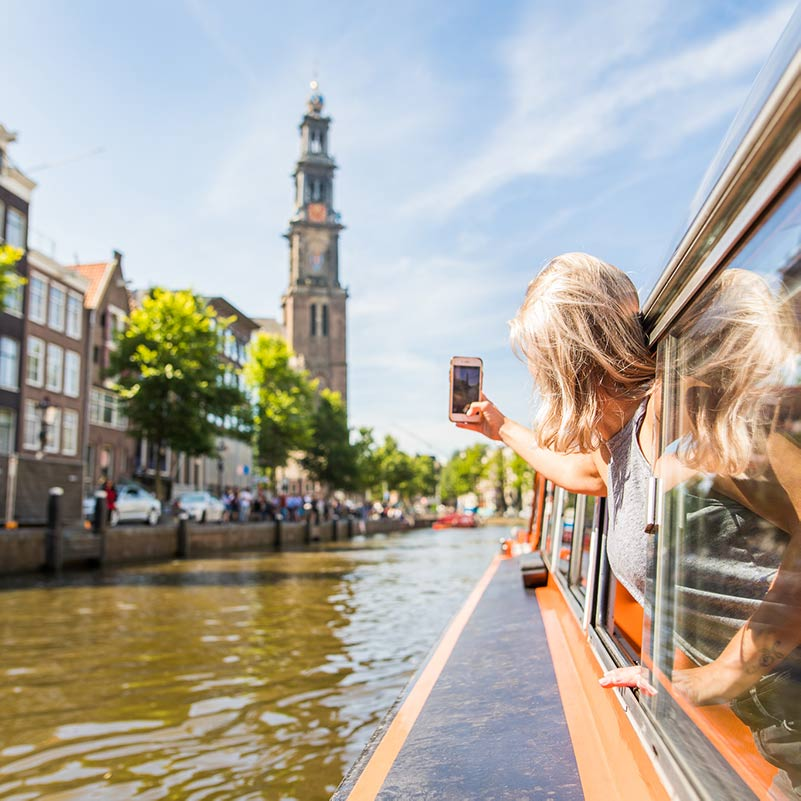 Woman taking a picture through the window of an Amsterdam Canal Cruise boat.