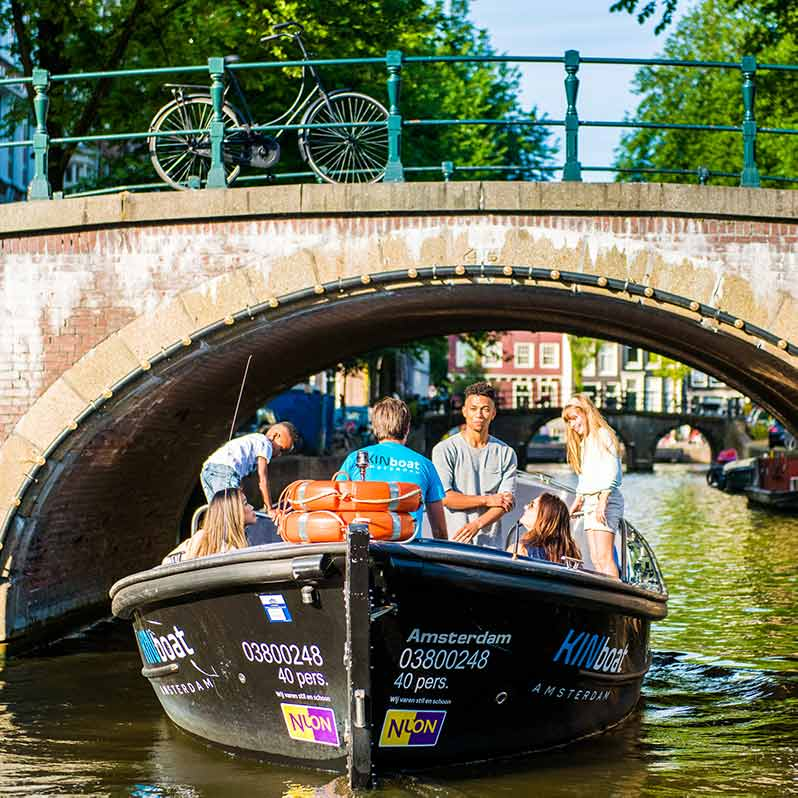 The Small Boat emerges from under a bridge with a few people in the boat.