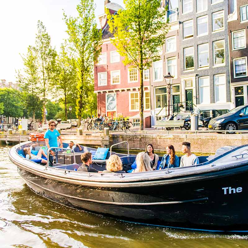 People on the small boat with an open roof sailing on the Amsterdam Canals.