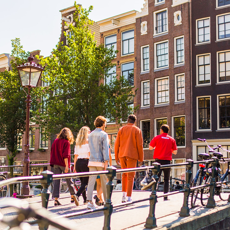 Five people following a guide on a bridge during the Amsterdam walking tour.