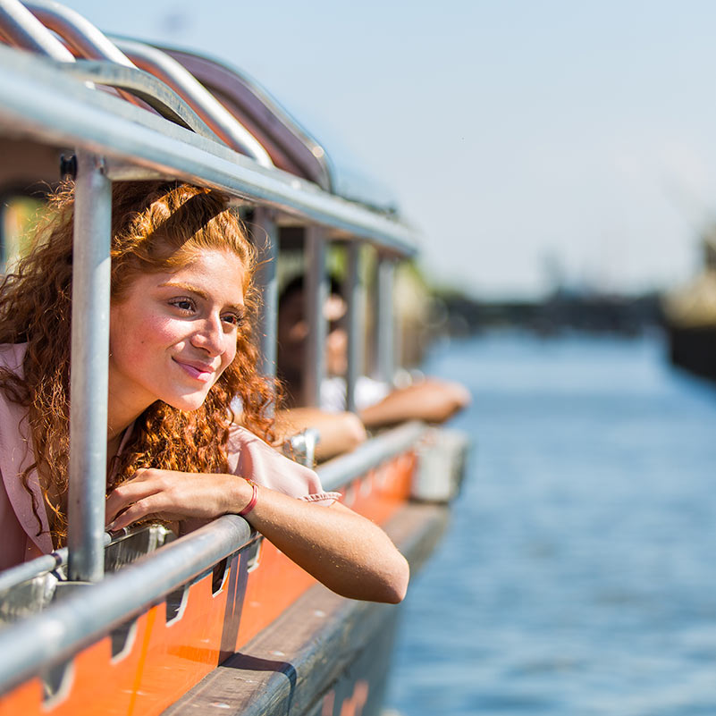 Woman leaning through a window of the Semi-open boat cruise and smiling.