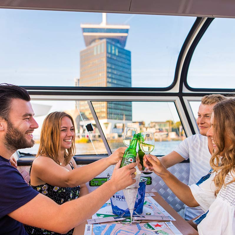Four people sitting at a table on the Amsterdam pizza and burger cruise toasting with wine and beer.