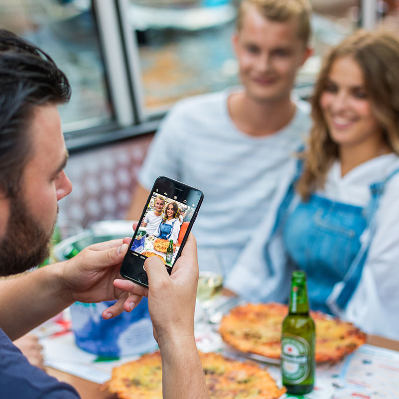 Guy taking a picture of two people sitting opposite him during the Amsterdam Pizza Cruise.