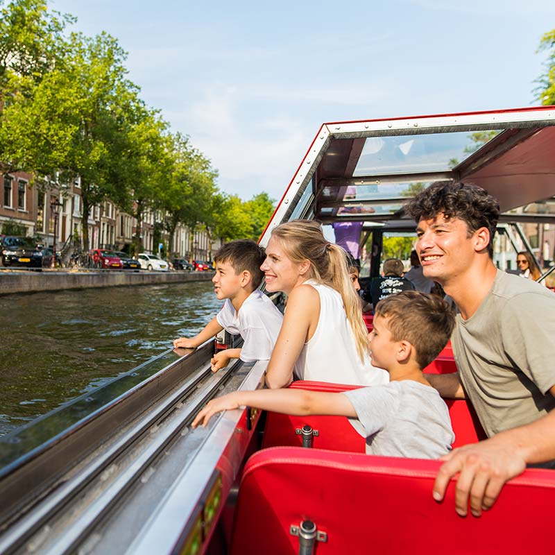 Two adults and two children sitting in the Hop on Hop off boat on the Amsterdam canals looking at the scenery.
