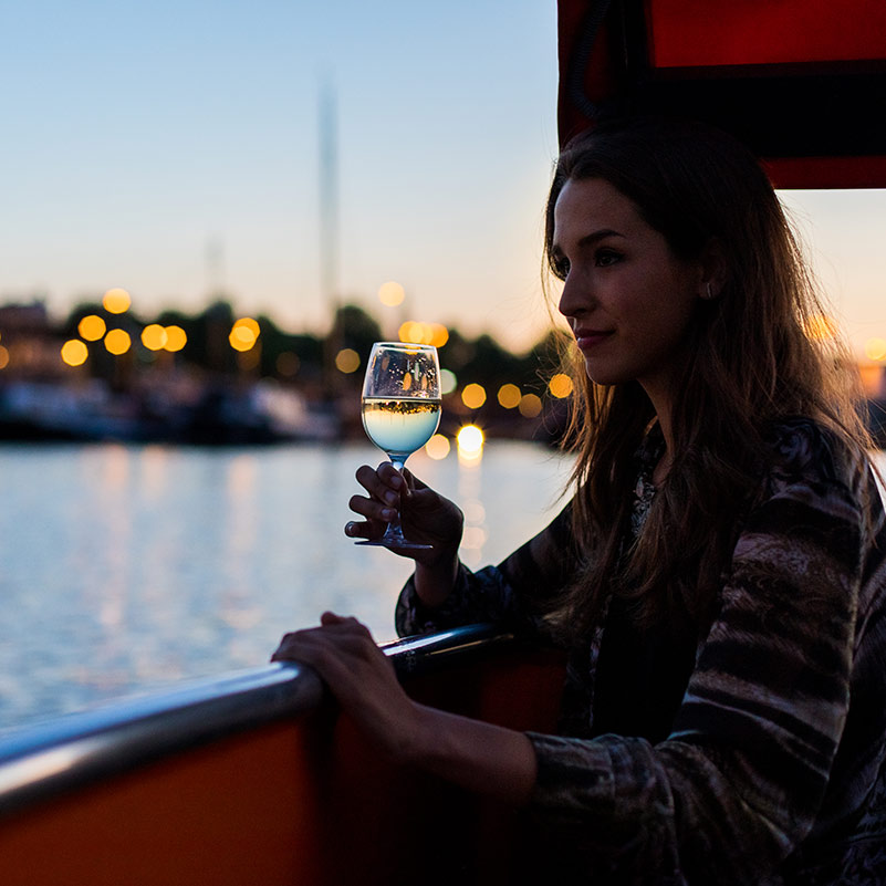 A women with a glass of wine looks out over the Amsterdam canals from a boat.