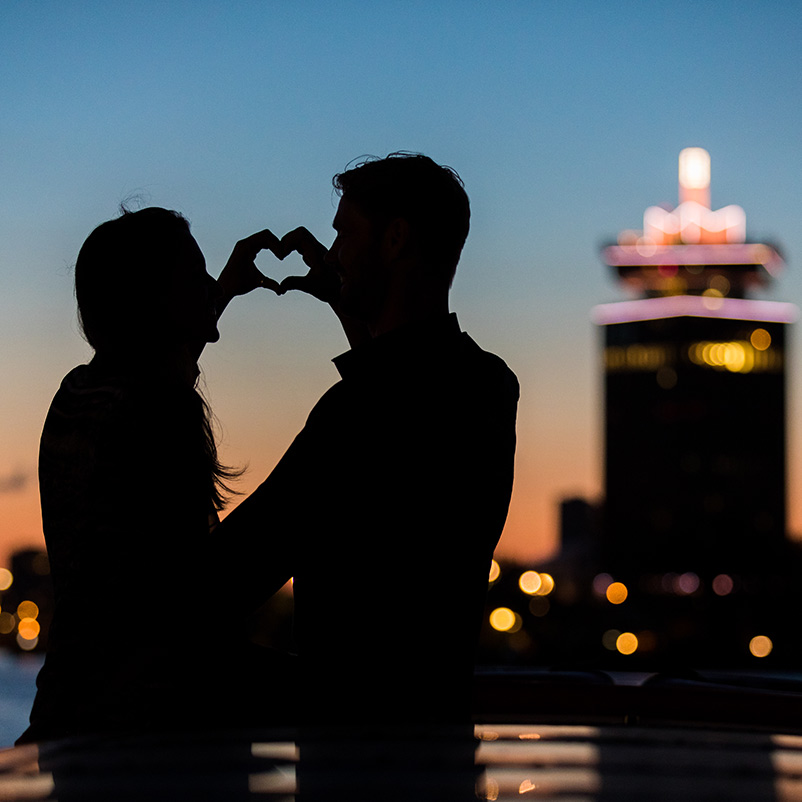Silhouette of two people making a heart shape with their hands with the A'Dam Tower in the background.