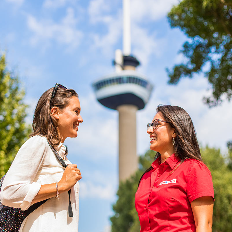 A woman talking to a guide from the Rotterdam, Delft & The Hague tour in front of the Euromast in Rotterdam.