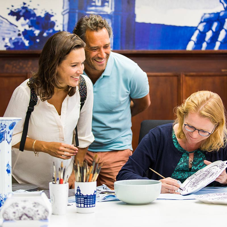 A man and a woman looking at a woman painting a Delft blue plate at the Royal Delft Blue experience.