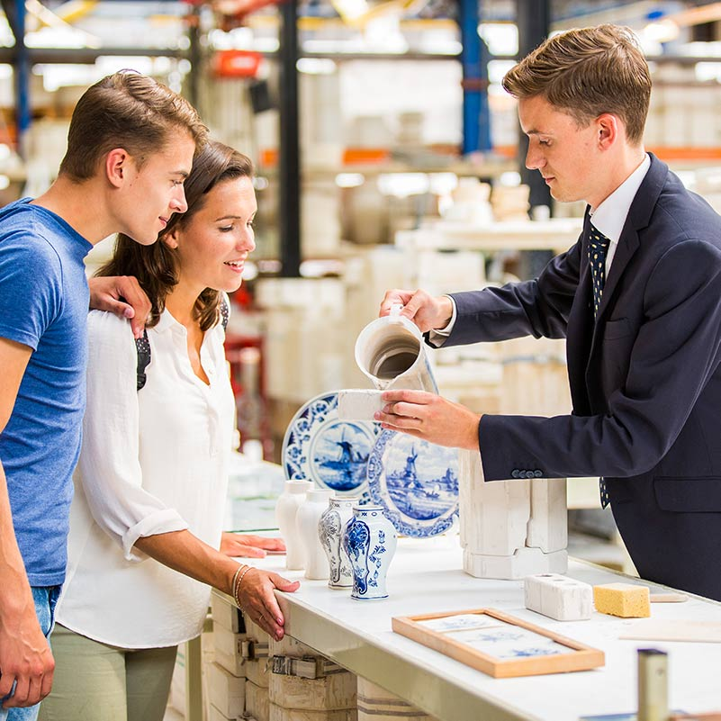 A man and a woman looking at a man showing them how to make Delft Blue ceramics at the Royal Delft factory.