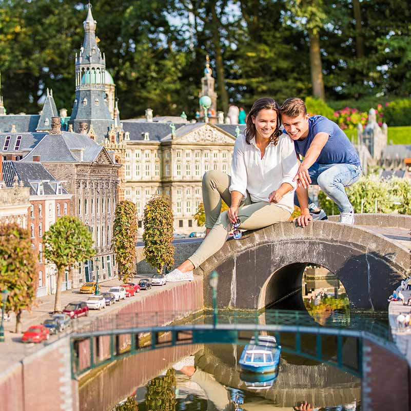 A woman and a man sitting on a miniature bridge in Madurodam during the Best of Holland Tour.