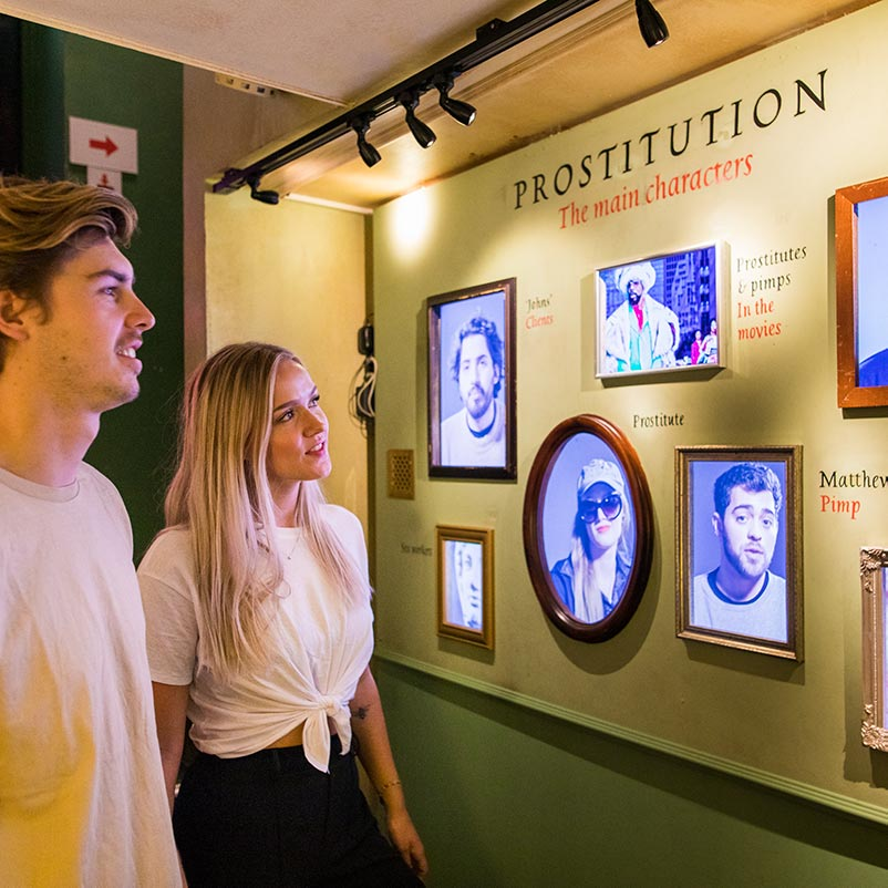 A woman and a men looking at a wall with pictures in the Prostitution museum Amsterdam.