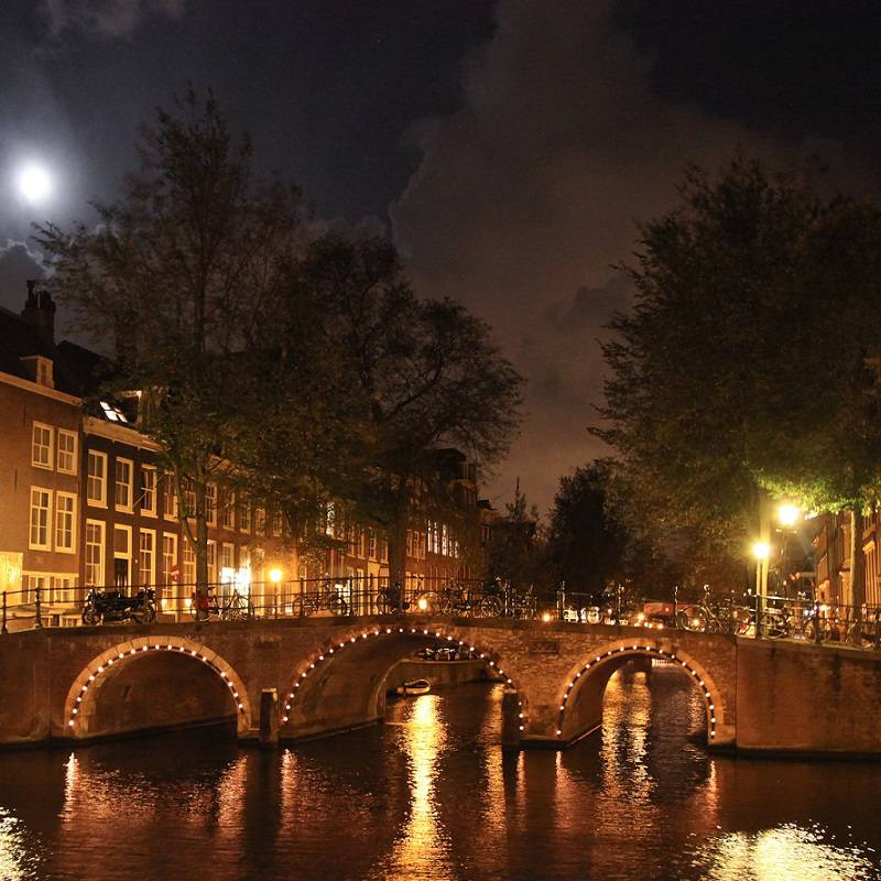 A bridge over an Amsterdam canal lit up in the dark.