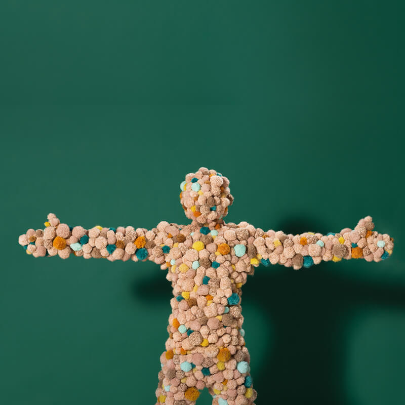 A green background with a statue of a person covered in fabric balls.
