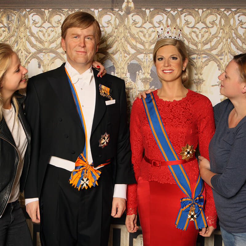 Two people standing next to the wax figures of King Willem-Alexander and Queen Maxima at Madame Tussauds Amsterdam.