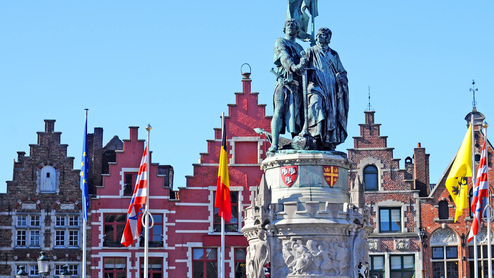 A statue of two men in Brugge with flags in the background.