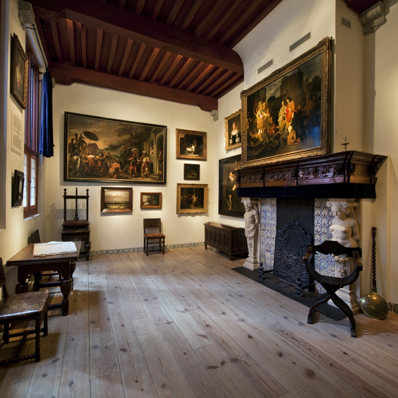 Inside of the Rembrandt House Museum with a fireplace and multiple paintings.