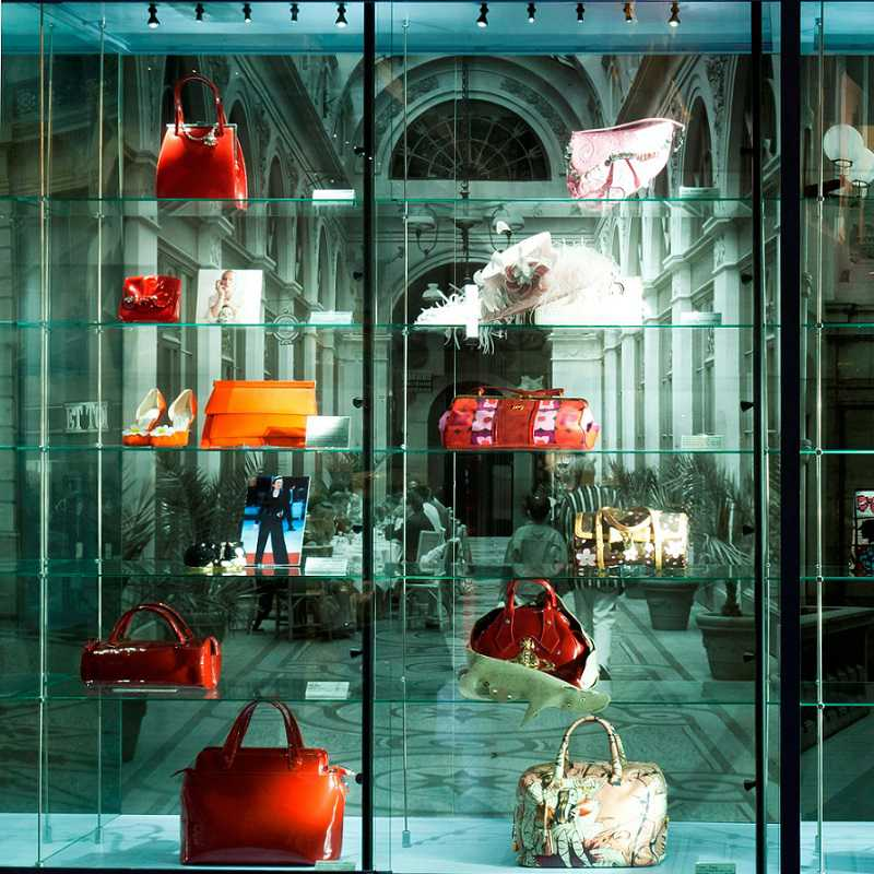 A display at the Museum of bags and purses with many bags in a glass cabinet.